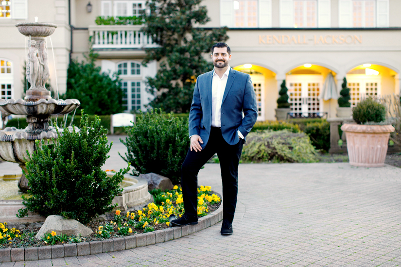 Ali Pourghadir stands with one foot up on the raised edge of a garden and fountain plot