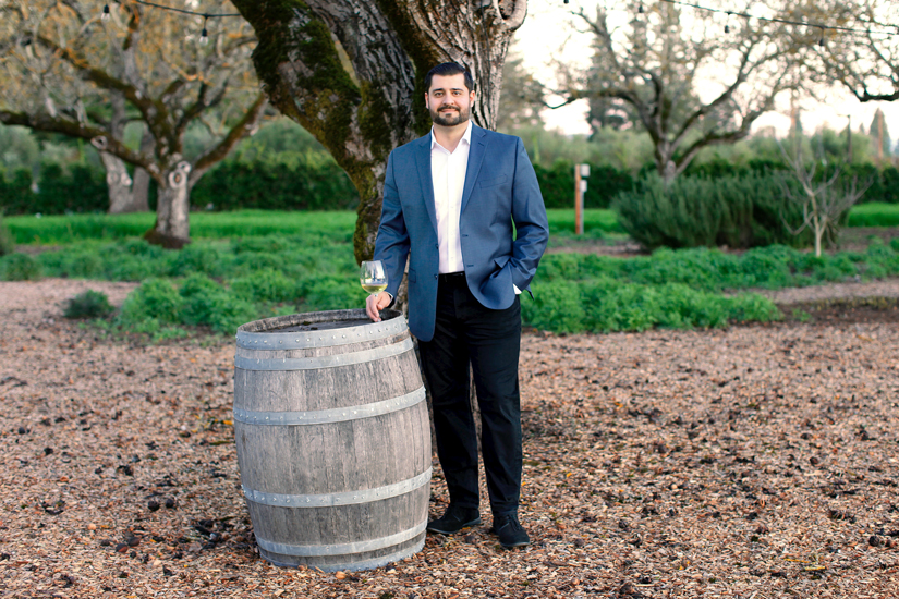 Ali Pourghadir stands next to an old barrel with a wine glass in his right hand