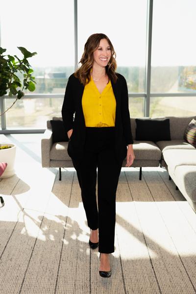 Dara Engle smiles and walks through a sunny lobby area