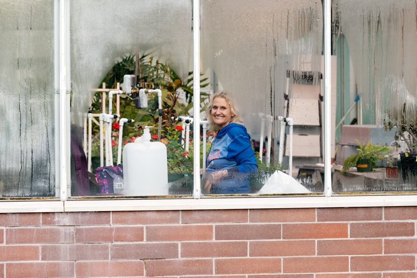 Tami Cox stands inside of a greenhouse at Boise State University.