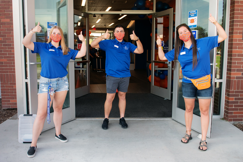Three resident assistants give thumbs up at the entrance to a Boise State University residence hall.